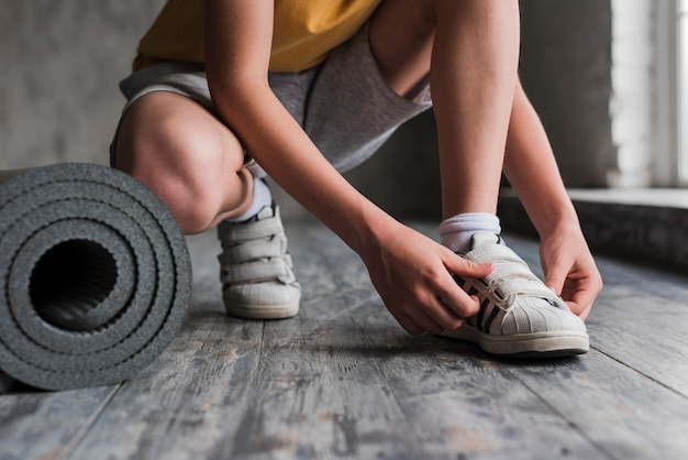 Low section of a boy putting his shoe strap near the rolled up exercise mat Free Photo