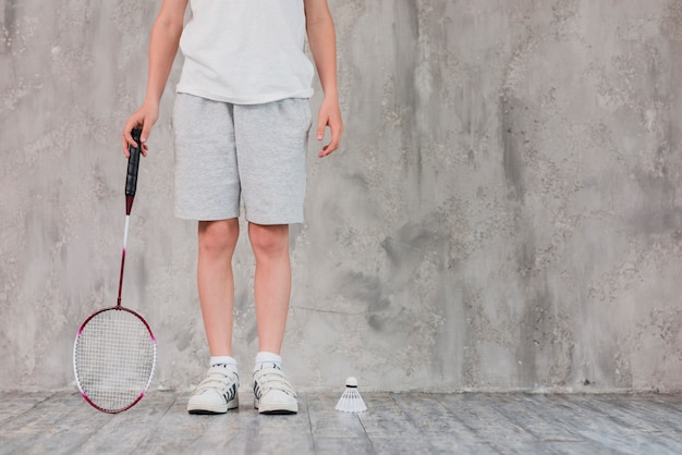 Low section of a boy standing with racket and shuttlecock Free Photo