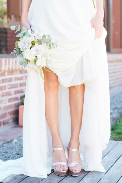 Low section of a bride holding flower bouquet in hand showing her fashionable high heels Free Photo