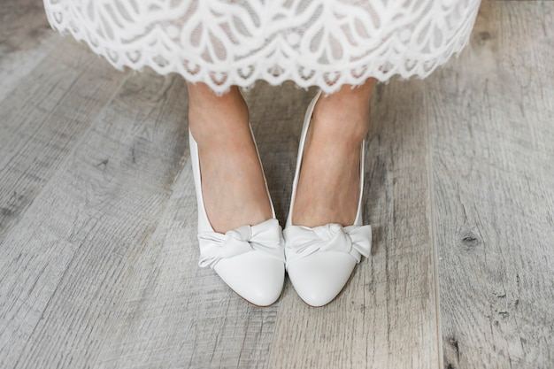 Low section of bride's leg wearing white dress shoes Free Photo