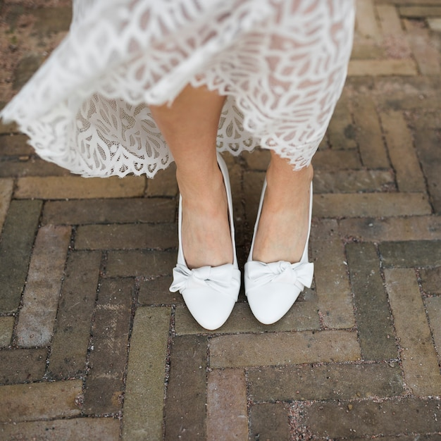 Low section of bride's leg wearing white heels Free Photo