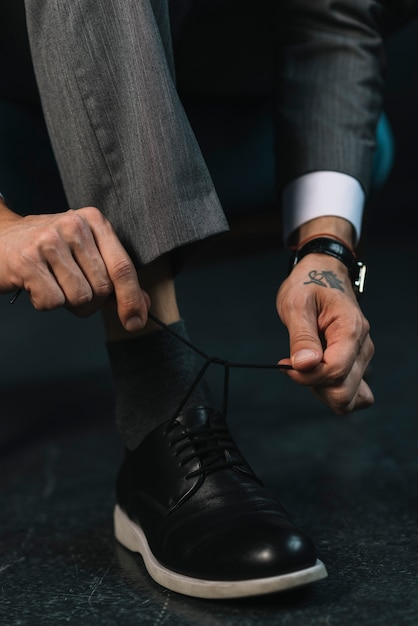 Low section of businessman's hand tying shoelace Free Photo
