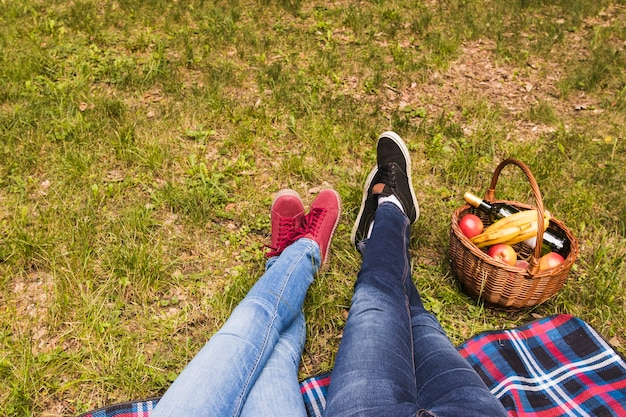 Low section of couple's leg on green grass with picnic basket Free Photo