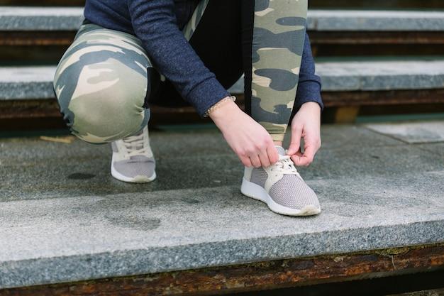 Low section of female jogger tying shoelace Free Photo