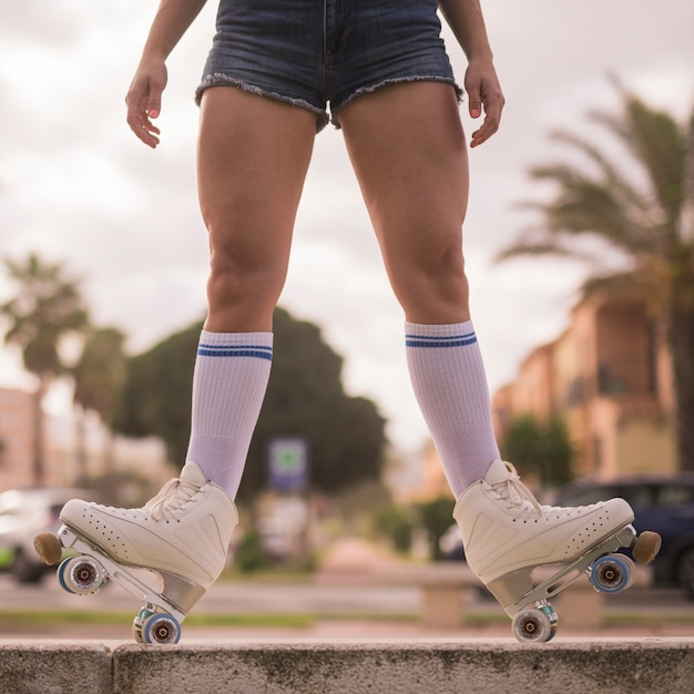 Low section of a female skater balancing on the bench Free Photo