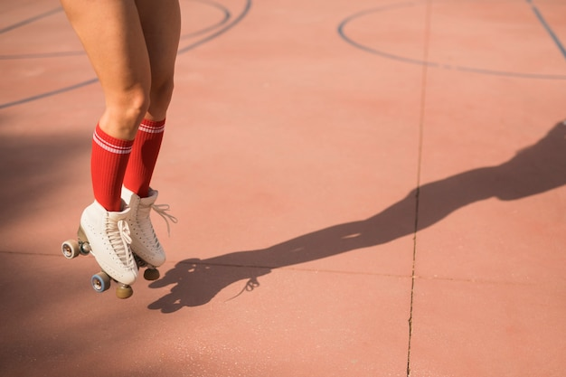 Low section of female skater jumping in air on court Free Photo