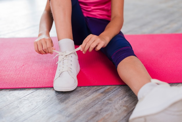 Low section of a girl sitting on exercise mat tying shoelace Free Photo