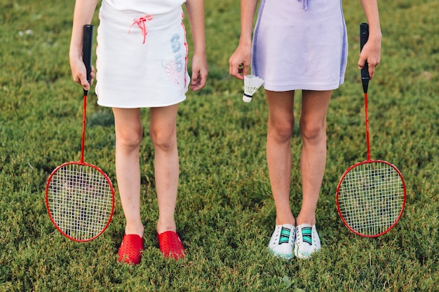 Low section of a girl standing on green grass holding badminton and shuttlecock Free Photo