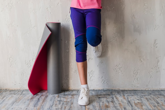 Low section of a girl standing near the rolled up exercise mat Free Photo