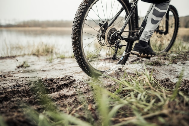 Low section of male cyclist riding bicycle in mud Free Photo