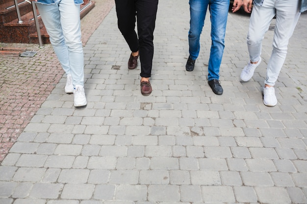 Low section of male friends walking together on pavement Free Photo