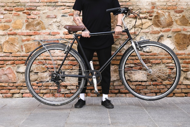 Low section of a man holding bicycle with his two hands Free Photo
