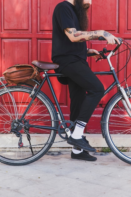 Low section of a man sitting with bicycle in front of door Free Photo