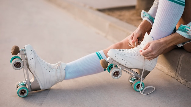Низкая часть женщины, завязывающая кружево роликовых коньков Premium Фотографии