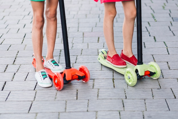 Low section of two girls standing on kick scooter Free Photo