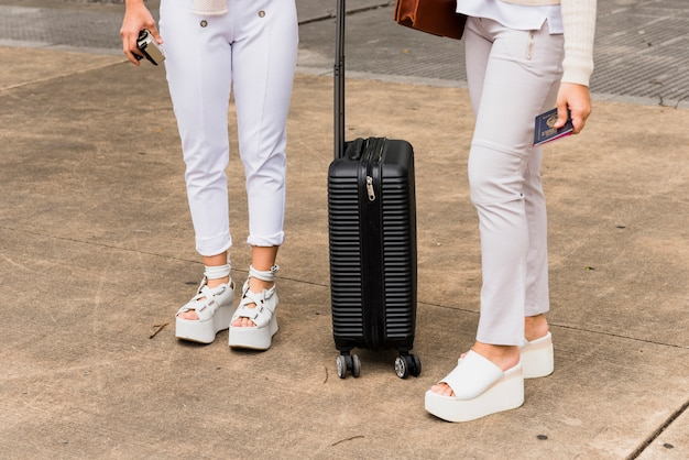 Low section of two young women standing with black suitcase Free Photo