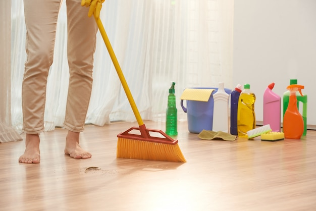 Low section of unrecognizable woman sweeping floor with broom Free Photo