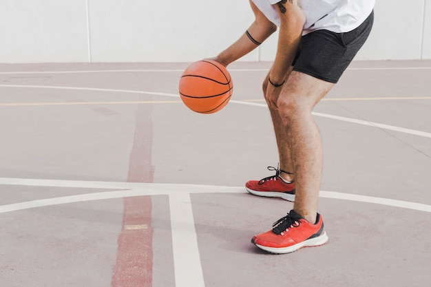 Low section view of a man practicing basketball in court Free Photo
