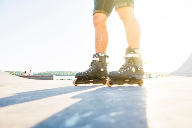 Low section view of a man rollerskating in skate park during summer Free Photo