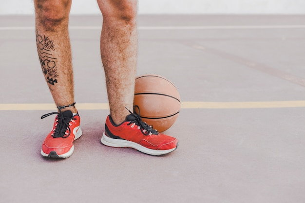 Low section view of a man's feet with basketball Free Photo