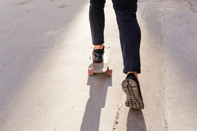 Low section view of a person's feet skating on wooden skateboard Free Photo