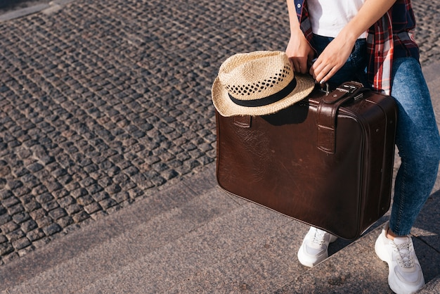 Low section of woman carrying brown luggage bag with hat standing on staircase Premium Photo
