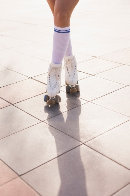 Low section of woman in roller skate standing with crossed legs on floor Free Photo