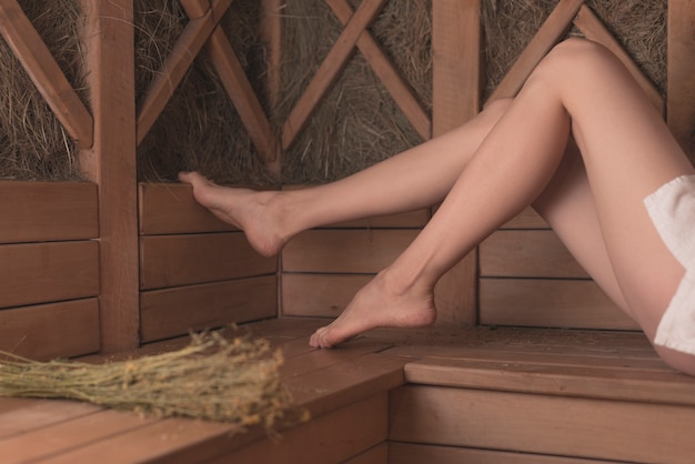 Low Section Of Woman S Feet On Wooden Bench In Sauna Photo