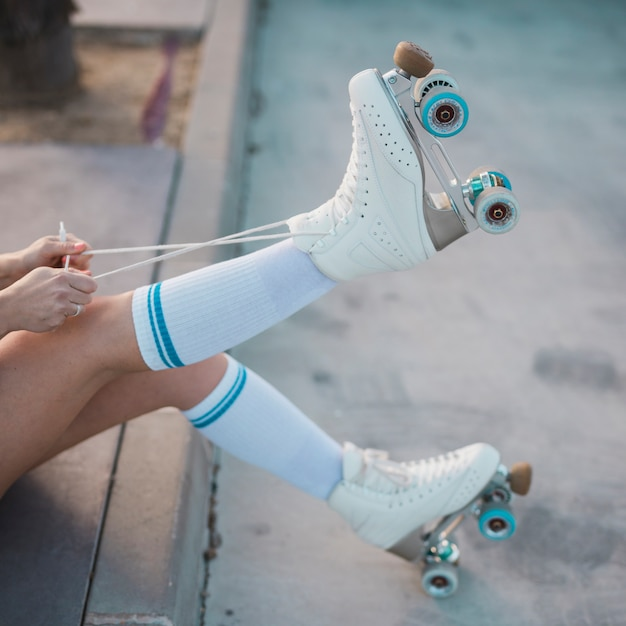 Low section of woman tying the lace of roller skate on the road Free Photo