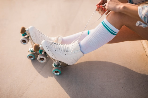 Low section of woman tying roller skate lace Free Photo
