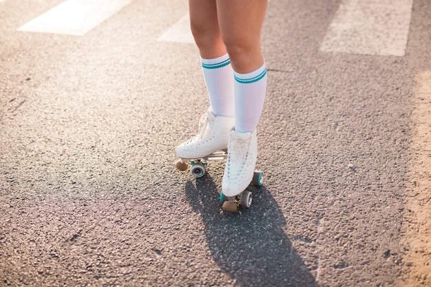 Low section of a woman wearing roller skate standing on asphalt Free Photo