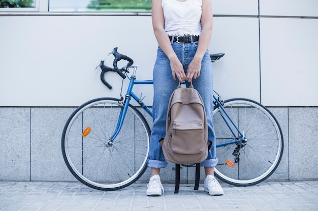 Low section of young woman holding backpack in her hand standing against bicycle Free Photo