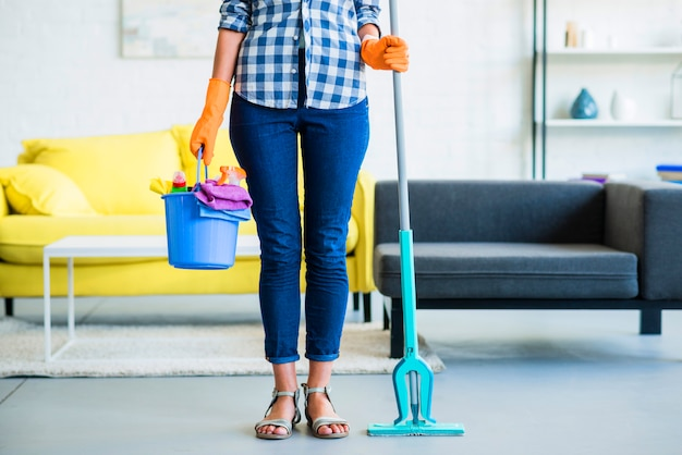 Low section of young woman holding bucket with cleaning supplies and mop Free Photo