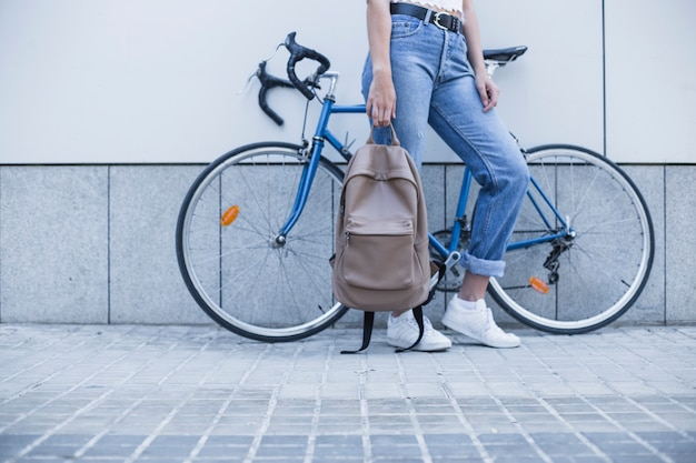 Low section of young woman standing near the bicycle holding backpack Free Photo