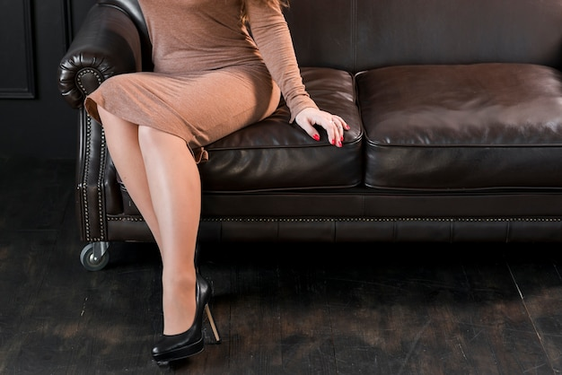 Low section of a young woman with black high heels sitting on sofa Free Photo