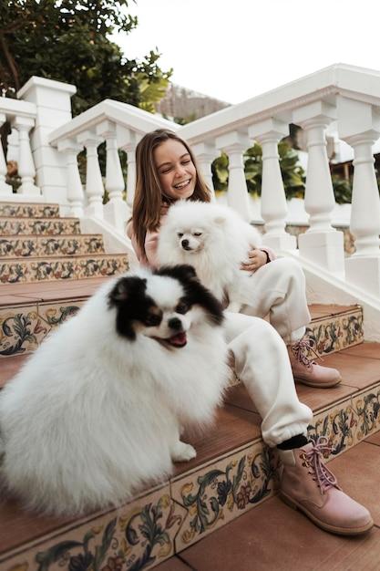 階段の上の低ビューの女の子と彼女の犬 無料写真
