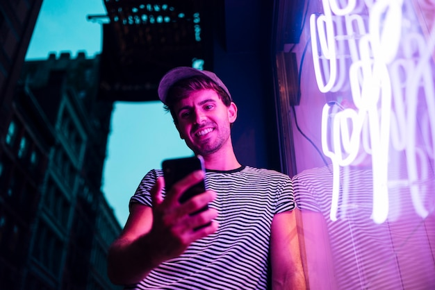 Low view of man looking at his phone and smile Free Photo