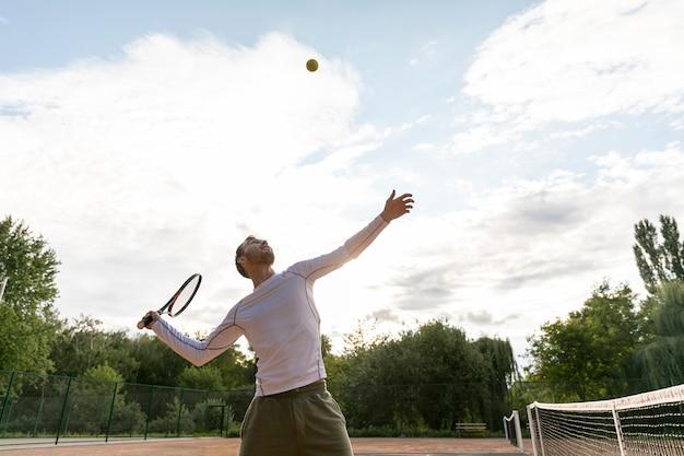 Low view man serving during tennis match Free Photo