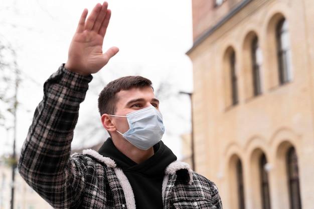 手で手を振っているマスクを身に着けている低ビューの男 無料写真