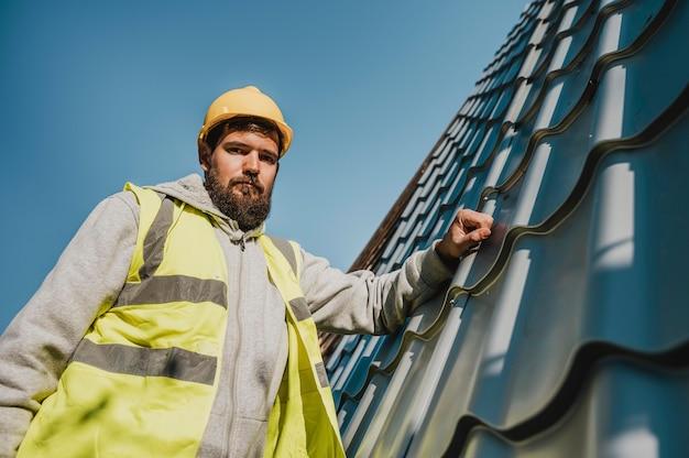 ドリルで屋根に取り組んでいるロービューの男 無料写真