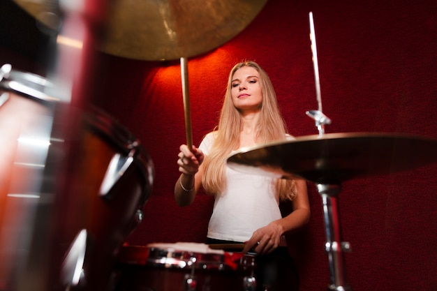 Low view shot of girl playing the cymbals Free Photo