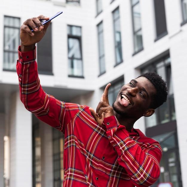 Inquadratura bassa dell'uomo che prende un selfie Foto Gratuite
