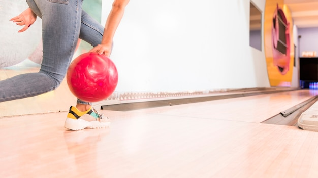 Low view woman throwing bowling ball Free Photo