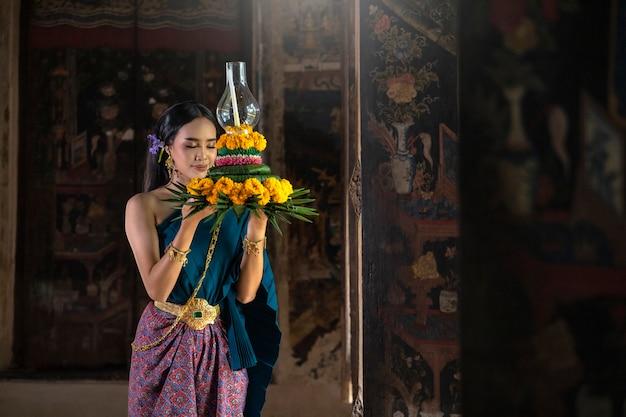 Фестиваль лой кратонг в таиланде. азиатские женщины - loy krathong для золота bless the buddha color. Premium Фотографии