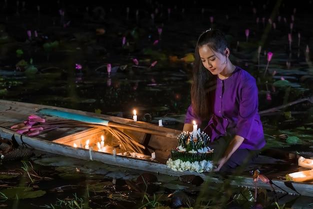 Фестиваль лой кратонг в таиланде. азиатские женщины лой кратонг на лодке в лотосовом пруду. Premium Фотографии