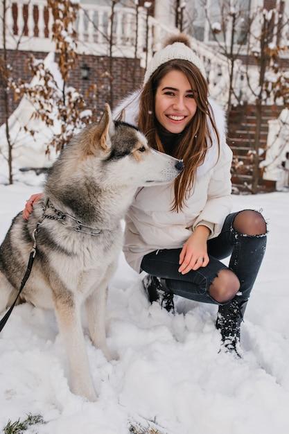 冬の日、白いジャケットを着た女性を撫でながら笑っている忠実な犬。雪に覆われた地面にハスキーでポーズのジーンズで壮大なヨーロッパの女性。 無料写真