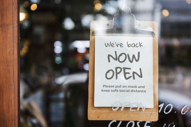 'we're back, now open' cafe sign after covid-19 pandemic Free Photo