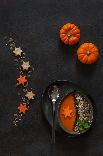 Ltraditional pumpkin homemade cream-soup with seeds crackers and little pumpkins. Premium Photo