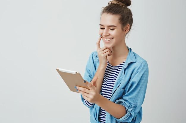 Удачливая милая женщина выигрывает билеты в онлайн-лотерею кино, смотрит довольным довольным цифровым экраном дисплея планшета, радостно развлекается. Бесплатные Фотографии