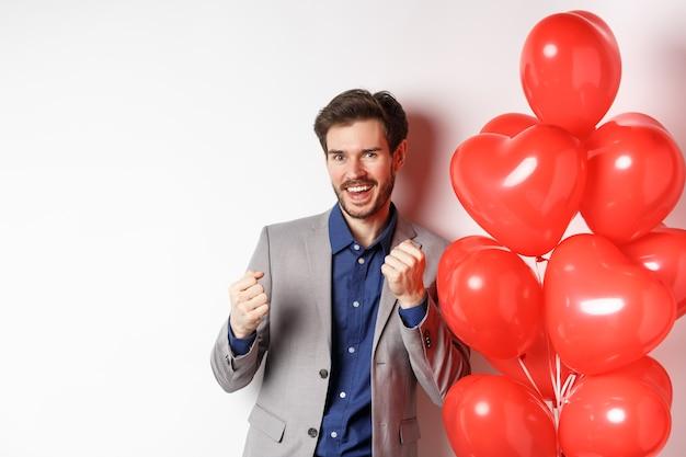 행운의 잘 생긴 남자 춤과 예, 연인의 날 심장 풍선 근처에 서 웃고, 흰색 배경에 서. 프리미엄 사진
